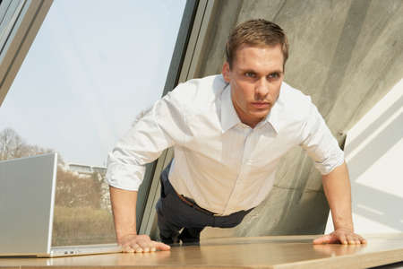 rolled up sleeves: Businessman doing push-ups in the office