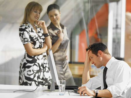 only three people: Businessman sitting in front of a desktop PC and two businesswomen looking at him LANG_EVOIMAGES