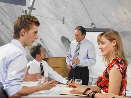 rolled up sleeves: Three businessmen and a businesswoman in a meeting