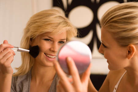 self conceit: Close-up of a young woman applying blush with another young woman holding a mirror