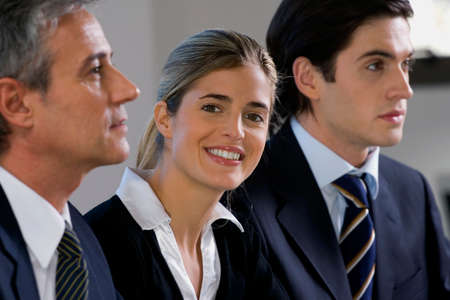 three people only: Portrait of a businesswoman smiling with two businessmen beside her