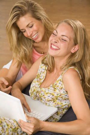 female bonding: Two young women using a laptop and smiling LANG_EVOIMAGES