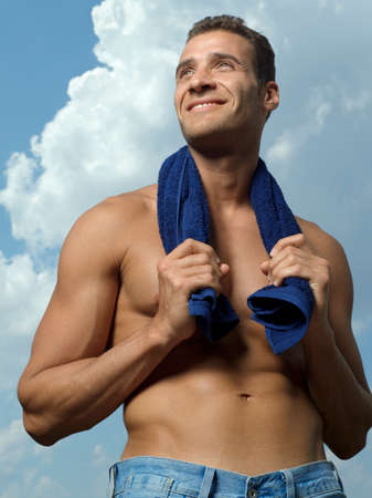 turkish ethnicity: Low angle view of a young man holding a towel around his neck and smiling