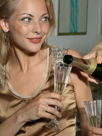 champagne flute: Close-up of a persons hand pouring champagne into a champagne flute held by a young woman