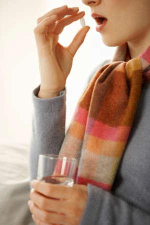 tomando refresco: Perfil lateral de una mujer adulta mediados de tomar una p�ldora LANG_EVOIMAGES