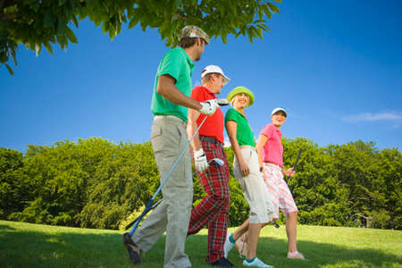 mid adult couples: Side profile of two mid adult couples walking on a golf course