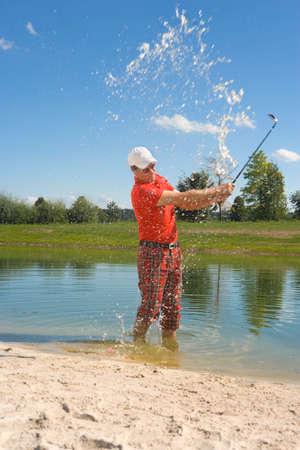 at waterhole: Perfil lateral de un hombre de mediana edad golpeando una pelota de golf en el pozo de agua en un campo de golf