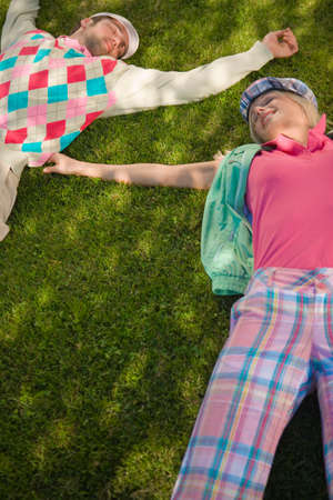 mid adult couple: High angle view of a mid adult couple lying on grass