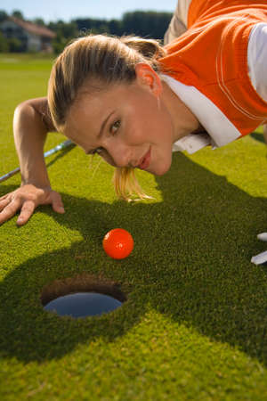 judging: Portrait of a mid adult woman judging a golf ball on a golf course