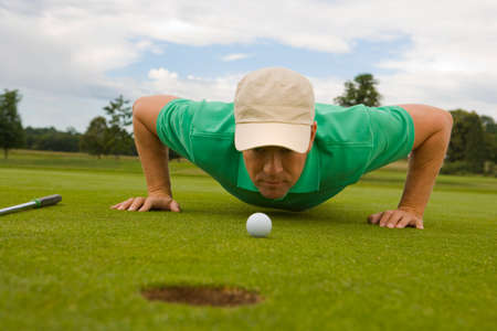 judging: Mid adult man judging a golf ball on a golf course LANG_EVOIMAGES