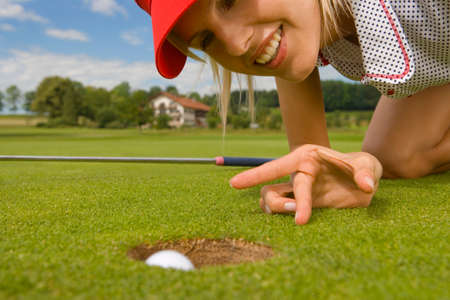 kneel down: Close-up of a mid adult woman putting a golf ball into a hole