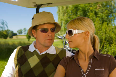 mid adult couple: Close-up of a mid adult couple sitting in a golf cart LANG_EVOIMAGES