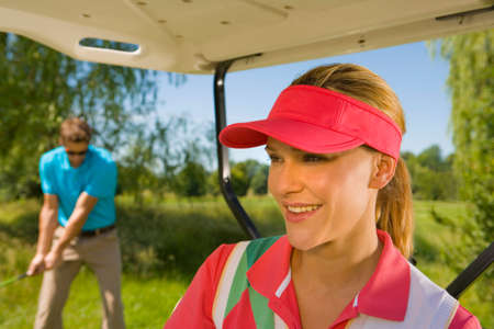 golf cart: Close-up of a mid adult woman smiling in a golf cart with a mid adult man playing golf in the background