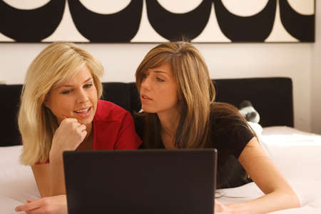 double chin: Two young women lying in front of a laptop LANG_EVOIMAGES