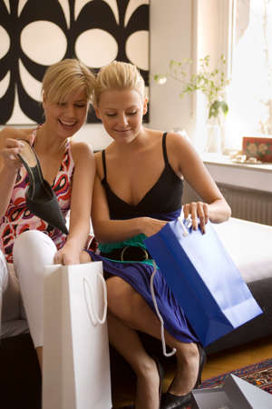two people only: Two young women sitting with shopping bags and smiling
