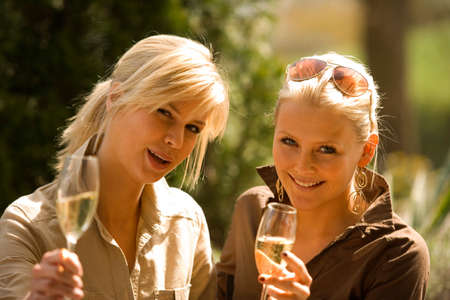 champagne flutes: Portrait of two young women holding champagne flutes and smiling LANG_EVOIMAGES