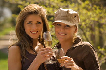 champagne flutes: Portrait of two young women holding champagne flutes LANG_EVOIMAGES