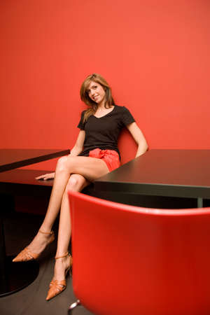 table skirt: Young woman sitting on a table and looking away