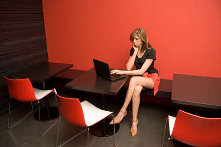 table skirt: Young woman sitting in a restaurant and using a laptop