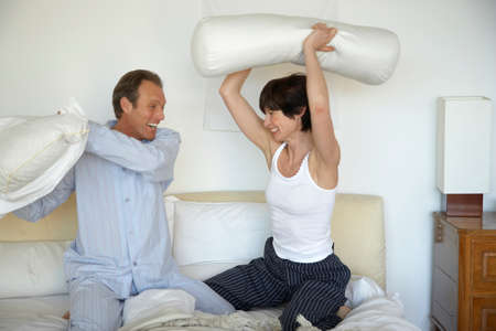 receding hairline: Mature couple having a pillow fight on the bed