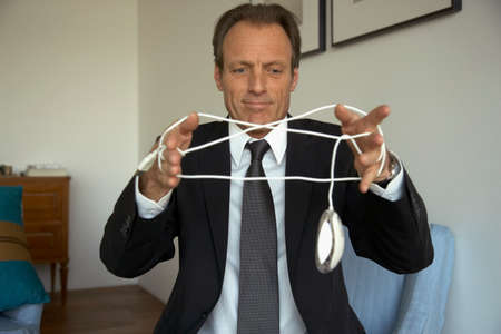 receding hairline: Mature man tangled in a computer mouse wire LANG_EVOIMAGES