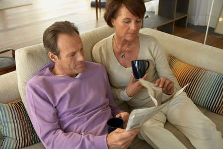 receding hairline: Mature couple reading a newspaper