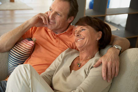 receding hairline: Close-up of a mature couple sitting on a couch