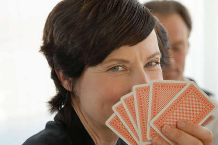 obscuring: Woman holding playing cards close to her face