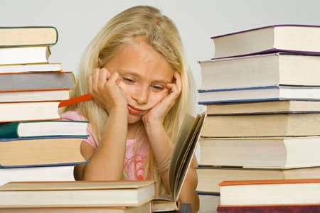 overburdened: Close-up of a girl sitting at a table and reading a book LANG_EVOIMAGES