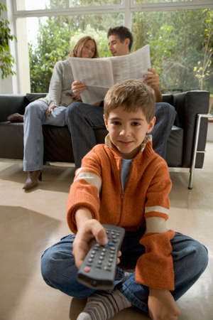 Boy with TV remote control and parents with newspaper in background Stock Photo
