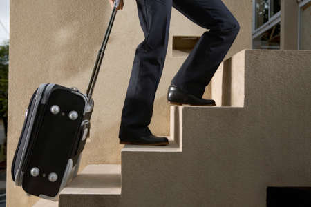 waist down: Person pulling luggage up stairs