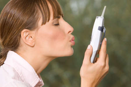 only mid adult women: Woman kissing the phone LANG_EVOIMAGES