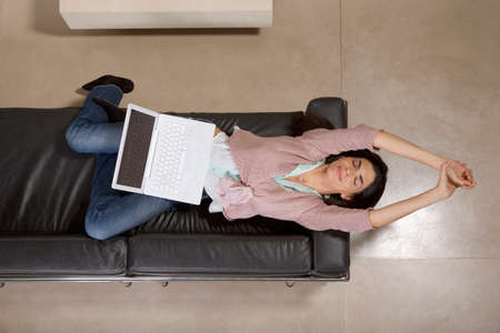 woman lying down: Woman lying down with laptop computer LANG_EVOIMAGES