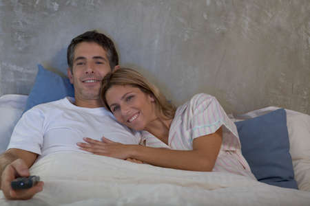 pareja viendo tv: Pareja viendo la televisi�n juntos en la cama