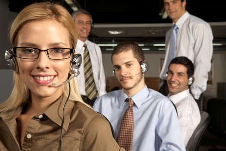 servicio al cliente: Retrato de un representante de servicio al cliente mujer sonriente con sus cuatro colegas detr�s de ella LANG_EVOIMAGES
