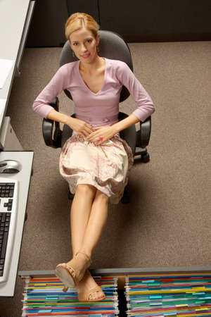 office cabinet: Young woman sitting in an office chair with her legs on a filing cabinet drawer LANG_EVOIMAGES