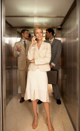 telephoning: Businesswoman using a mobile phone with two businessmen standing behind her in an elevator