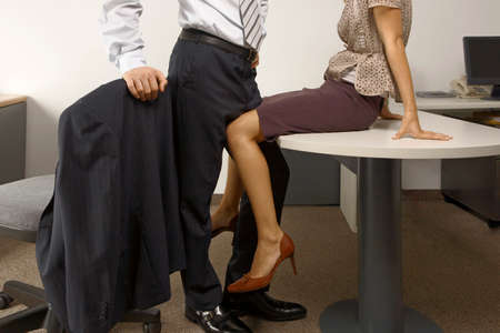 low section view: Low section view of a businessman and a businesswoman flirting in an office