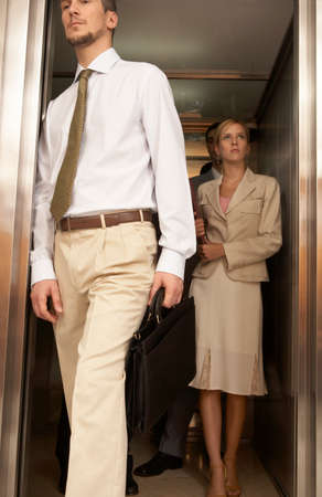 exiting: Businessman exiting from an elevator with a businesswoman standing behind him