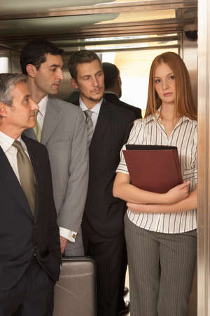 women's issues: Three businessmen looking at a businesswoman standing in an elevator