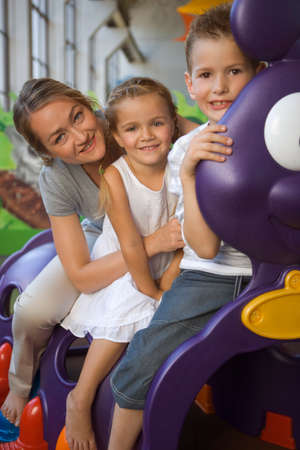children caterpillar: Portrait of a mid adult woman with two children sitting in a caterpillar train