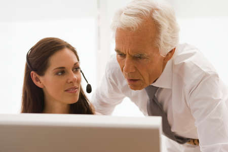 receding hairline: Businesswoman wearing a headset with a businessman looking at a computer monitor in an office