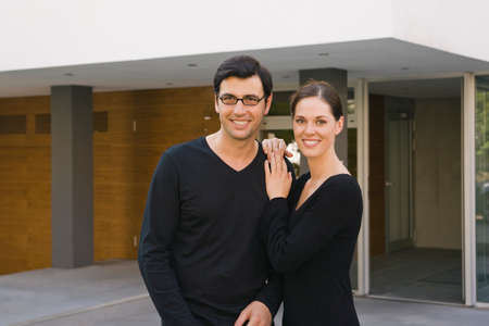 mid adult couple: Portrait of a mid adult couple standing in front of a building and smiling