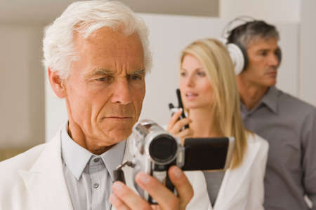 only three people: Close-up of a senior man looking at a digital video camera