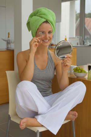 curler: Woman with eyelash curler and hand mirror LANG_EVOIMAGES