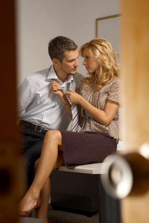 business woman legs: Businessman and a businesswoman flirting in an office