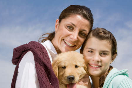 one teenage girl only: Portrait of Mother and Daughter holding puppy LANG_EVOIMAGES