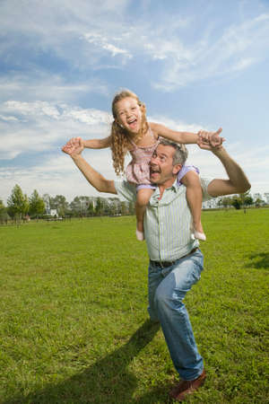 age 40 45 years: Happy father with daughter on his shoulders LANG_EVOIMAGES