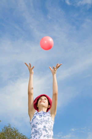 waist down: Girl throwing pink ball in air