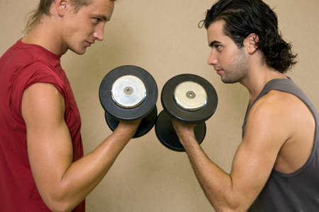 young men: Side profile of two young men exercising with dumbbells LANG_EVOIMAGES
